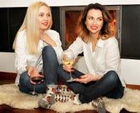 2 женщины сидя на ковре меха на камине Стоковые Фотографии RF
