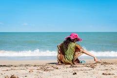 Женщины сидя на пляже Стоковые Изображения