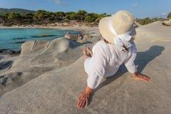 Женщины сидя на скалистом пляже на красивом утре Стоковое Изображение