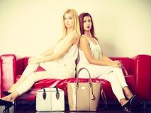 2 женщины сидя на софе представляя сумки Стоковая Фотография RF