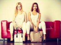 2 женщины сидя на софе представляя сумки Стоковое Изображение