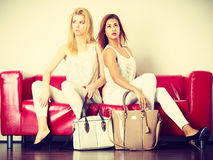 2 женщины сидя на софе представляя сумки Стоковая Фотография