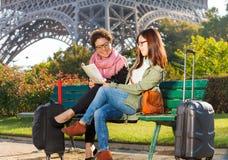Женщины сидя на стенде и читая карту Парижа Стоковое фото RF