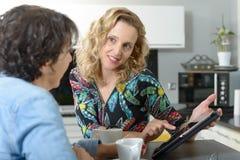 2 женщины сидя на таблице в кухне и используя таблетку Стоковое фото RF