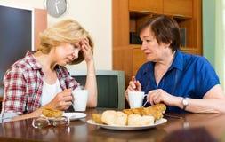 2 женщины сидя на таблице и выпивая чае Стоковые Изображения