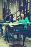 2 женщины сидя на таблице на улице Стоковая Фотография