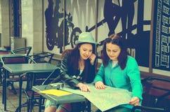 2 женщины сидя на таблице на улице Стоковое Фото