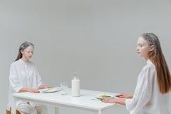 2 женщины сидя на таблице с едой Стоковые Фотографии RF