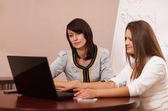 2 женщины сидя на таблице с компьтер-книжкой Стоковые Изображения