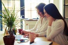 2 женщины сидя на таблице с тетрадью Стоковые Изображения
