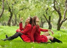 2 женщины сидя на траве Стоковые Фото
