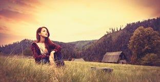 Женщины сидя на траве Стоковые Изображения