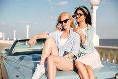2 женщины сидя на tohether автомобиля в лете Стоковое Фото