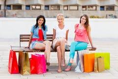 Женщины сидя после ходить по магазинам Стоковая Фотография