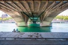 2 женщины сидя под мостом около реки Стоковые Изображения