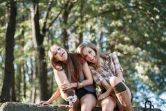 2 женщины сидя смеяться над совместно Стоковые Изображения RF