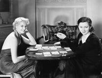 2 женщины сидя совместно играя карточки (все показанные люди более длинные живущие и никакое имущество не существует Th гарантий  Стоковая Фотография RF