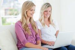 Женщины сидя совместно на кресле с усмехаться компьтер-книжки Стоковое Фото