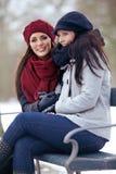 2 женщины сидя Outdoors на холодной зиме Стоковое фото RF