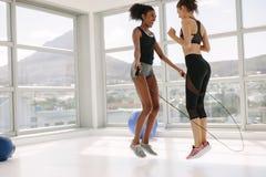 Женщины скача вместе с прыгая веревочкой в спортзале стоковое фото