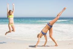 2 женщины скача на пляж Стоковые Фотографии RF