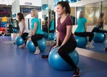 Женщины скача на шарик тренировки во время группы тренируют Стоковое Изображение RF