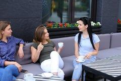 Женщины смеясь над и говоря на кафе, выпивая кофе Стоковое фото RF