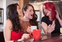 Женщины смеясь над с мобильным телефоном Стоковые Фотографии RF