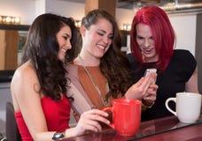 Женщины смеясь над с мобильным телефоном Стоковое фото RF