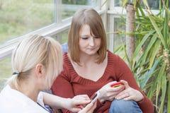 2 женщины смотрят в их собственный умный телефон Стоковое фото RF