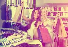 2 женщины смотря возбужденный и нося много бумажных сумок в fashio Стоковое Изображение