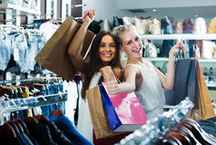 2 женщины смотря возбужденный и нося много бумажных сумок в fashio Стоковая Фотография