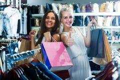 2 женщины смотря возбужденный и нося много бумажных сумок в fashio Стоковые Фото