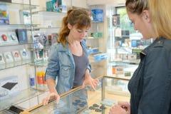 Женщины смотря в стеклянный счетчик в магазине стоковая фотография rf
