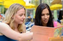 Женщины смотря книгу или меню совместно Стоковые Изображения RF