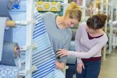 Женщины смотря материал на крене стоковая фотография