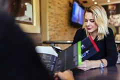 2 женщины смотря меню Стоковые Изображения