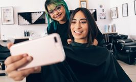 Женщины смотря мобильный телефон на салоне Стоковые Фотографии RF