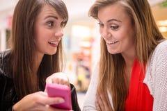 2 женщины смотря мобильный телефон Стоковые Фото