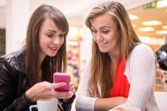 2 женщины смотря мобильный телефон Стоковое фото RF