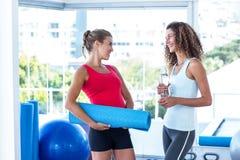 Женщины смотря один другого пока держащ циновку и бутылку с водой тренировки Стоковые Изображения