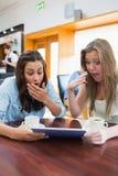 Женщины смотря удивленный пока держащ таблетку Стоковое Изображение