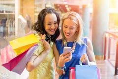 2 женщины смотря smartphone пока ходящ по магазинам Стоковая Фотография