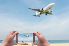 Женщины снимая изображение с умным телефоном на голубом море и белизне Стоковые Изображения
