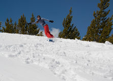 Женщины сноубординга холм вниз снежный в горах стоковые изображения rf