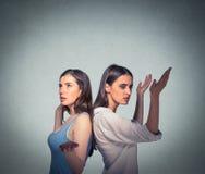 2 женщины спина к спине кладя руки в воздух смотря вверх в фрустрации Стоковое Изображение