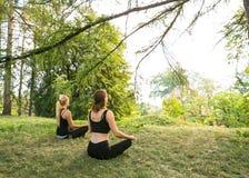 Женщины спорта делая йогу снаружи в утре Стоковые Фото