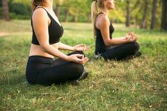 Женщины спорта делая йогу снаружи в утре Стоковое Фото