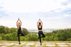 Женщины спорта делая йогу снаружи в утре Стоковое фото RF