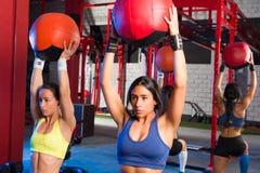 Женщины спортзала утяжелили тренировку разминки шарика стоковое фото